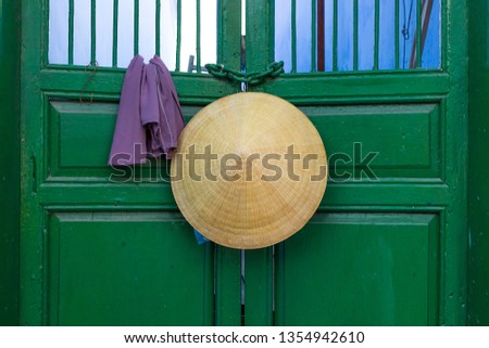 Asian style conical hat hanging on a green door in Hoi An ancient town in Vietnam .