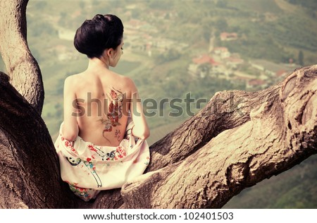 Asian style portrait of young woman sitting on the tree branch with snake tattoo on her back (original)