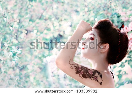 Asian style portrait of young woman with snake tattoo on her arm