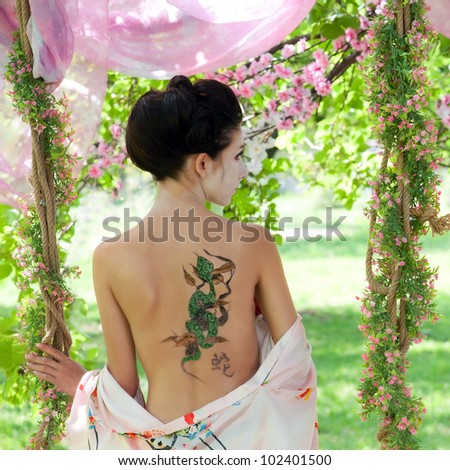 Asian style portrait of young woman with snake tattoo on her back