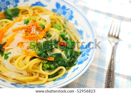 Asian style soup noodles cooked with a variety of vegetables to signify healthy lifestyle, food and beverage, and diet and nutrition concepts. - stock photo