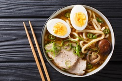 Asian style soup with udon noodles, pork, boiled eggs, mushrooms and green onions close-up in a bowl on the table. horizontal top view from above