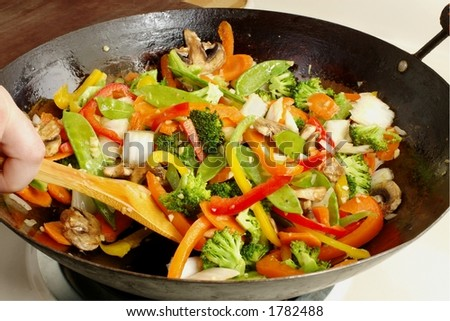 Asian-style stir-fry cooking in a well-used wok - stock photo