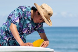 Asian Surfer putting in a yellow surf fin into a surf board in Japan with a blue ocean back ground the surfer is wearing a Hawaiian style shirt and straw hat. The fin is a US style centre Box fin.
