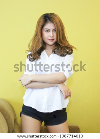 Stock Photo Asian sweet smiling girl pose on the sofa for relaxing on her holiday in her private room with yellow background