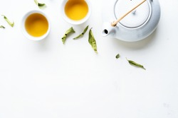 Asian tea concept, two white cups of tea and teapot surrounded with green tea dry leaves view from above, space for a text on white background.