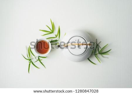 Asian tea concept, two white cups of tea and teapot surrounded with green tea dry leaves view from above, space for a text on white fabric background