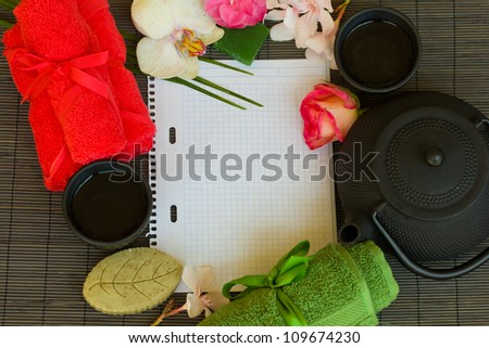 asian tea set and spa settings with blank note book on bamboo mat