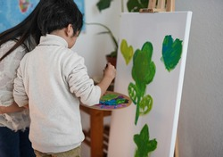 Asian teacher and little child painting on canvas - Creative activities in school classroom