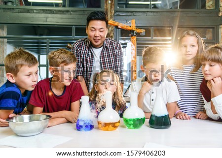 Asian teacher doing experiments with dry ice for children at classroom in modern school. During experiment scientist holds flask showing reaction smoke and colored liquid.