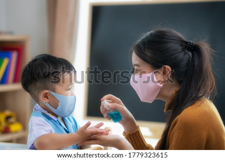 Asian teacher use bottle spray to spray alcohol liquid to hands of her student for prevent corona virus covid 19 in in her class room, in preschool. Stock photo ©