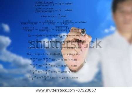 Asian teacher writing scientific formula on the whiteboard.