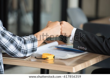 Asian team businessman or partners  business people giving fist bump (punching fists or clash of two fists) after complete a deal in the office, fist bump colleagues collaboration, teamwork concept. #617856359