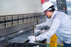 Asian technician worker wearing a safety suit and sheet Metal Bending in industrial factory, Safety first concept.