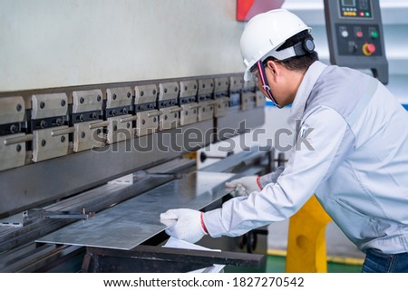 Asian technician worker wearing a safety suit and sheet Metal Bending in industrial factory, Safety first concept. Foto d'archivio ©