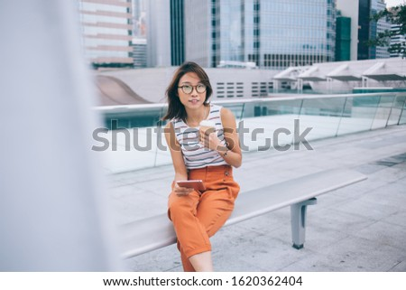 Asian teen student teen in stylish outfit and eyeglasses sitting holding takeaway coffee and cell phone at street of Hong Kong city looking at camera