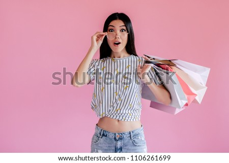 Asian teenage girl on pink background. Stylish young woman with shopping bags in hands