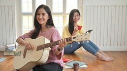 Asian teenage girls are singing and playing guitars.They stay at home to prevent the corona virus outbreak.
