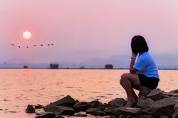 Asian teenage woman sit lonely alone at the waterfront looking at the beautiful nature landscape sun and flock of birds flying a row sunset at the lake background, Krasiao Dam, Suphan Buri, Thailand
