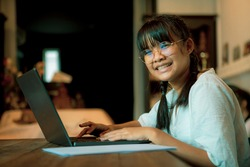 asian teenager typing on computer laptop keypad toothy smiling face to camera