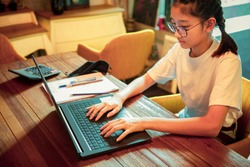 asian teenager working on computer laptop in home living room ,concept work from home while infection of covid-19 virus