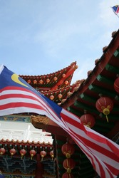 asian temple with malaysian flag in foreground