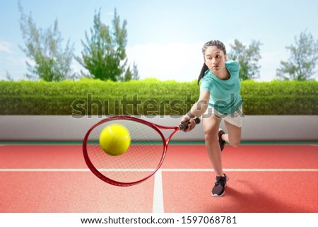 Asian tennis player woman swing the tennis racket her hands and play tennis on the tennis court