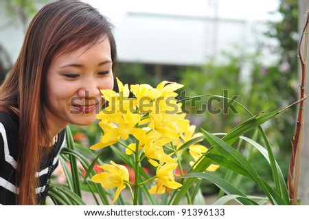 asian thai attractive woman in garden smelling flower