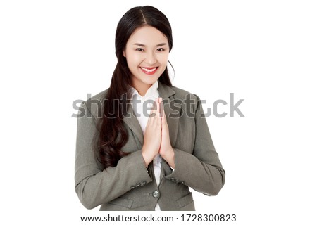 Asian Thai businesswoman wearing a black suit made a hello gesture calls Sawasdee or Was with a smiley face. Thai culture is  friendly greeting. studio head shot isolated. Сток-фото ©