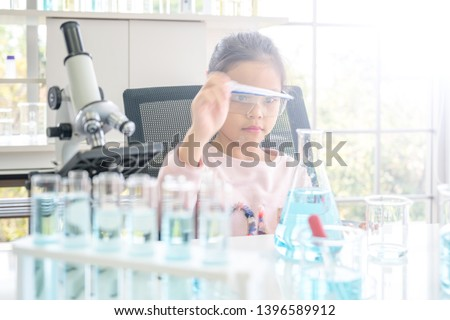 Asian Thai Children scientists making experiments chemical with looking microscope in the laboratory room.Science and education concept