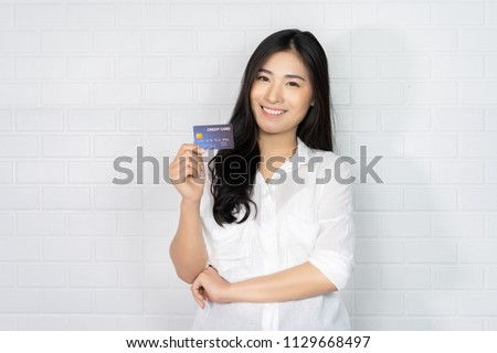 Asian Thai Elegant black girl blouse in home holding   credit-card signing up on a website application. Business Woman paying with a credit card while shopping online