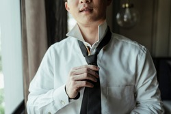 Asian thai man on white shirt dressing up and adjusting tie on neck at home. Neck tie dress up procedure.