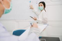 Asian thai nurse giving presentation to doctor inside hospital meeting room. Reading script on smartphone using internet.