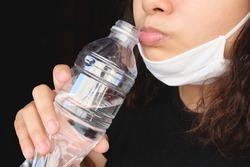 Asian Thai woman wearing a white cloth mask for prevent the Covid-19 or Corona virus and Air Pollution Value Pm 2.5 in Thailand and drinking a bottled mineral water. Health and illnes concept