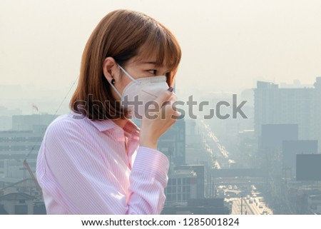 Asian Thai woman wearing the N95 Respiratory Protection Mask against air pollution at road and traffic in Bangkok, healthcare concept