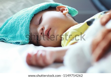 Asian toddler boy get sick,he has got high fever and sleeping on parent bed. He has wet blue towel on his forehead to relief the temperature.  Stockfoto ©
