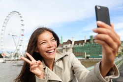 Asian tourist in London taking self-portrait photo smiling happy showing victory v hand sign with London Eye in background. Travel and tourism concept with beautiful girl travelling in London, England