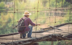 Asian tourist man walking on the old and broken wood bridge. Risks of travel concept