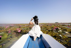 Asian tourist woman on a blue long tail boat at amazing Red lotus sea. unseen in Thailand, tourism Thailand, Udon Thani Province Thailand.