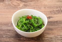 Asian traditional chukka salad in the bowl served red caviar