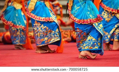 Asian travel background. Beautiful Balinese dancer woman in traditional Sarong costume dancing Legong dance. Legs movements. Arts, culture of Indonesian people, Bali island festivals.