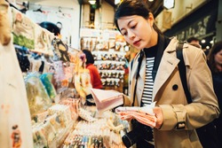 asian travel woman photographer buying souvenirs in Japanese handkerchief vendor in brocade market in kyoto japan. chinese tourist holding several pink mockets choosing in gift shop nishiki ichiba.