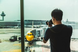 Asian traveler , business man hand holding DSLR or mirrorless camera to take a photo and waiting for his flight at the airport with airplane background