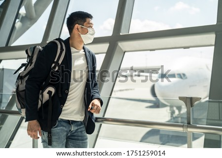Asian traveler business man wearing face mask waiting to board into airplane, standing in departure terminal in airport. Male passenger traveling by plane transportation during covid19 virus pandemic.