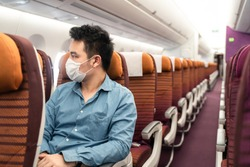 Asian traveler business man with sitting on aisle seat wearing face mask looking out of window on airplane in airport. Male passenger traveling by plane transportation during covid19 virus pandemic.