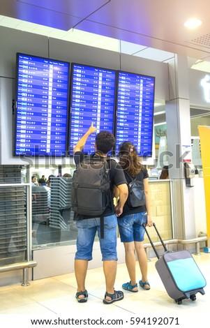 Asian traveler looking flight information screen board in airpor