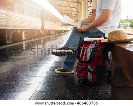 Asian traveler man with belongings waiting for travel by train at Chiang Mai train station, Thailand. Vintage effect - Shutterstock ID 486403786