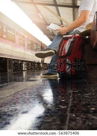 Asian traveler man with belongings waiting for travel by train at Chiang Mai train station, Thailand. - Shutterstock ID 563871406