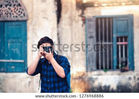 Asian Traveler wearing Blue Plaid Shirt Taking a Photo with Film Camera for Travelling in Bangkok , Thailand in Relax Emotion Lifestyle Travel Moment in Hollidays #1276968886