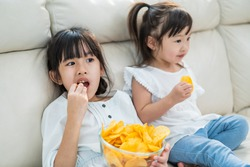 Asian Two sweet sisters little girl resting on sofa at home enjoy eating fast food, potato chips. Hungry preschool Cute kid Puts snack in mouth with hand. Tasty and unhealthy food for children concept